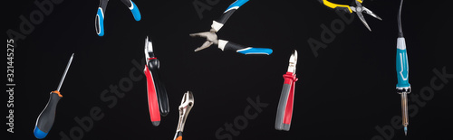 Photo Wrenches, screwdriver and pliers levitating in air isolated on black, panoramic