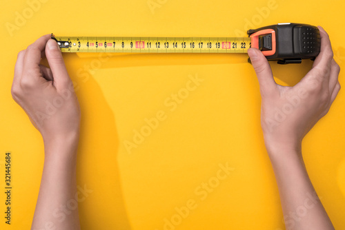 Obraz Top view of man holding industrial measuring tape on yellow background - fototapety do salonu
