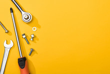 Top View Of Wrenches, Screwdriver And Bolts On Yellow Background