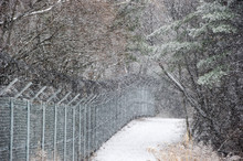 A Snowy Road By The Barbed Wire.