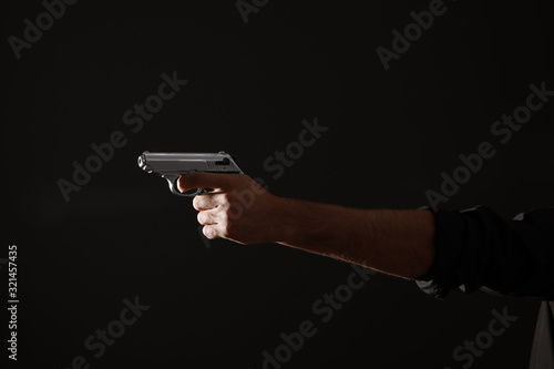 Fototapeta Professional killer with gun on black background, closeup obraz
