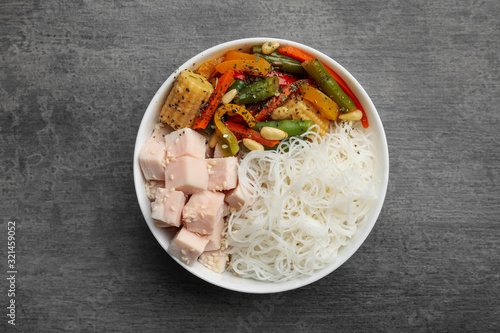 Fototapeta Tasty cooked rice noodles with chicken and vegetables on grey table, top view obraz