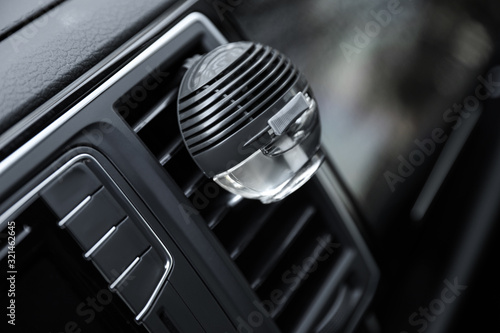 Photo Stylish air freshener clip attached to car ventilation