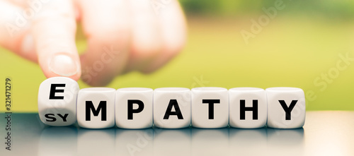 Fotografie, Obraz Hand turns dice and changes the word sympathy to empathy.
