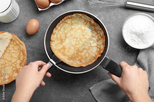 Fototapeta Woman holding frying pan with thin pancake at grey table, top view obraz