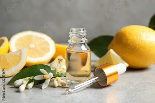 Fototapeta Citrus essential oil, flower and lemons on light table obraz