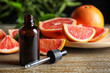 Leinwanddruck Bild Citrus essential oil and grapefruits on wooden table. Space for text