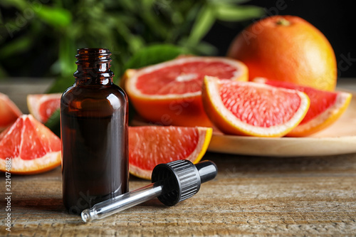 Fototapeta Citrus essential oil and grapefruits on wooden table. Space for text obraz