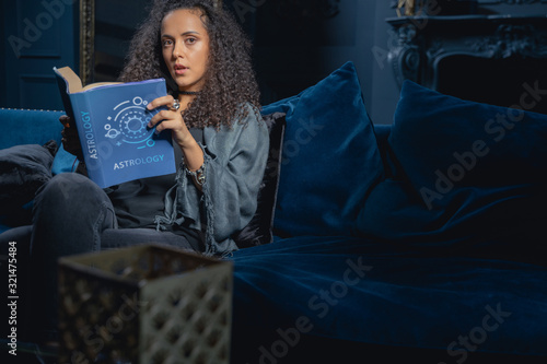 Photo Young female astrologer sitting on the couch