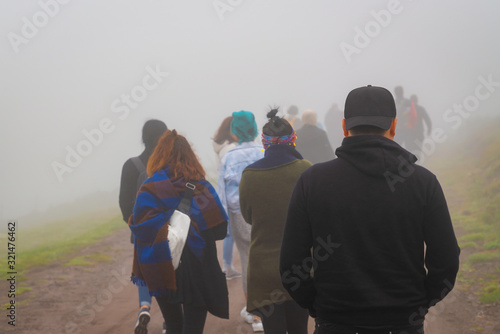 Fotografía Back view of refugees walk to the border in a cold day under fog