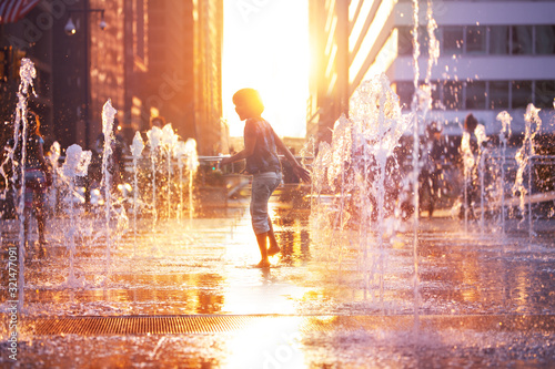 Fototapeta Child run and play on street fountain on Philadelphia square over sunset near city hall in downtown obraz