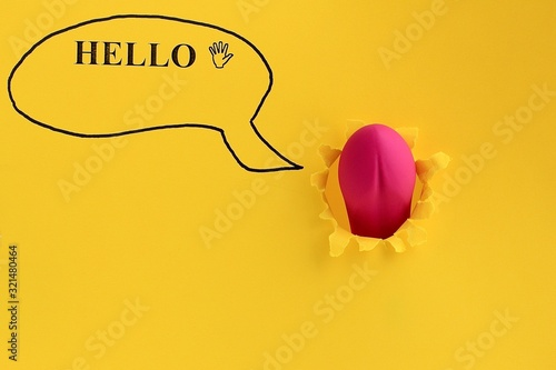 Foto Sex toy for adult, dildo vibrator looking through a hole in the yellow paper with text hello