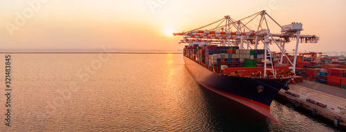 crane loanding cargo container to container ship in the international terminal yard port  concept freight shipping by ship at sunrise .