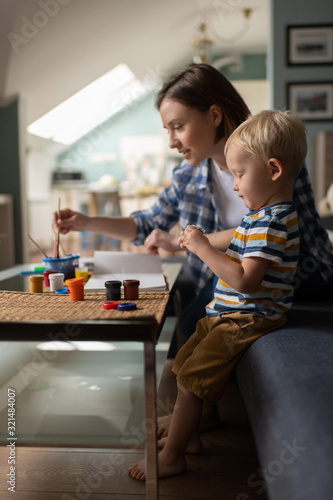 Female babysitter teaching little kid drawing at home Canvas Print