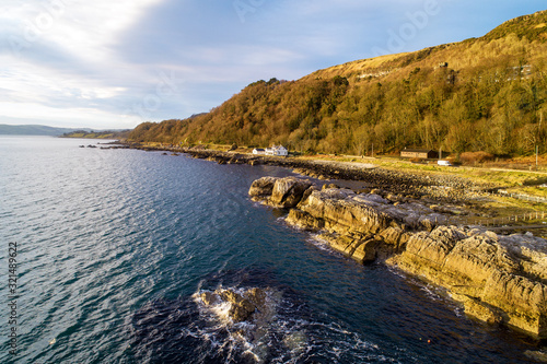 Northern Ireland, UK. Atlantic coast,  Garron Point rocks and Antrim Coast Road, a.k.a. Causeway Coastal Route. One of the most scenic coastal roads in Europe. Aerial view in sunrise light