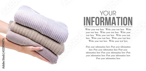 Fotografiet Stack folded sweater clothing hand holding on white background isolation, space