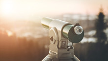 Future And Inspiration Concept: Tourist Binocular, Winter Landscape And Sunshine In Blurry Background.