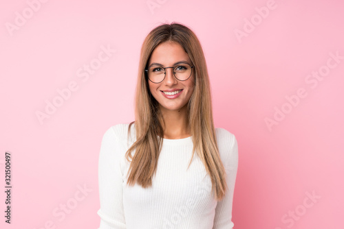 Young blonde woman over isolated pink background with glasses