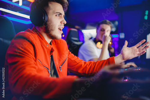 Fotografía Gamer young man is defeated in online video game, anger and facepalm, screaming and emotion, neon color