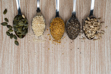 Top View Of Spoons Filled With Various Seeds On A Wooden Background. Plant Sources Of Omega 3 And 6 Fatty Acids. Chia, Flax, Pumpkin, Sunflower And Sesame Seeds As Part Of A Healthy Vegan Diet.