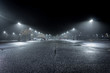 A Lonely Parking Lot on a Cold, Rainy Night - with a Small Collection of Parked Cars in the Background and a Thick Mist Gathering Under the Lights