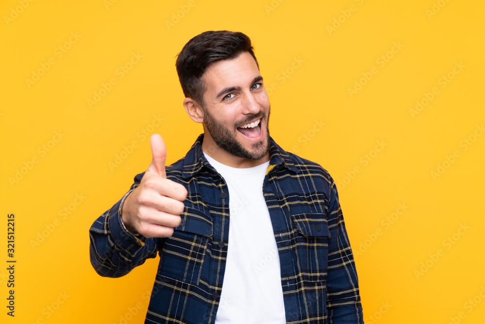 Fototapeta Young handsome man with beard over isolated yellow background with thumbs up because something good has happened