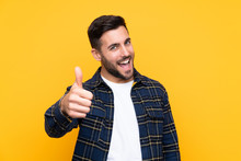 Young Handsome Man With Beard Over Isolated Yellow Background With Thumbs Up Because Something Good Has Happened