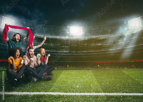 Soccer fans in the middle of the action during a night game at the stadium Canvas Print