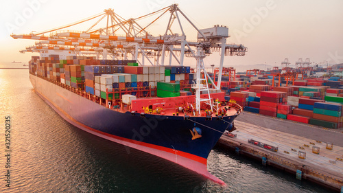 Fototapeta crane loanding cargo container to container ship in the international terminal yard port  concept freight shipping by ship at sunrise . obraz