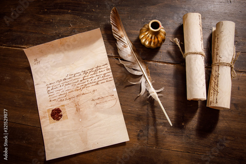 Photo Quill pen, feather with a letter and a scroll on a wooden table.
