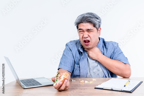 Asian middle aged man having symptoms of food stuck in his throat Since he eats hamburgers in a hurry While working on a wooden table, On white background, to health care and food concept Canvas Print