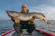 canvas print picture - Happy fisherman with big pike fish. Boat fishing
