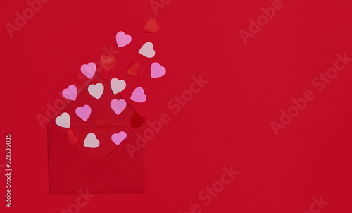 Red envelope with paper hearts. Romantic letter of declaration of love on a red paper background. Flat lay^ copy space fo text