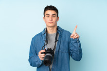 Teenager Photographer Man Isolated On Blue Background Pointing With The Index Finger A Great Idea