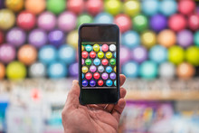 Hand Holding Smartphone Taking Picture Of Balloons At Fairground Booth
