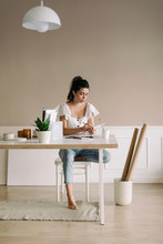 Young Woman Sitting At Table A...