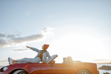 Woman Enjoying Beautiful Landscapes, Lying On The Car Hood While Travel On The Rocky Coastline On A Sunset. Side View With Copy Space On The Sky