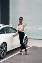 Portrait Of Young Woman Posing In Front Of Sports Car