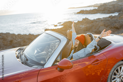 Portrait of happy woman with raised hands driving convertible car on the rocky ocean coast during a sunset Canvas Print