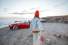 Woman In Red Hat Walking On The Rocky Coast Straight To The Ocean, Traveling By A Cabriolet During A Sunset. Follow Me Concept