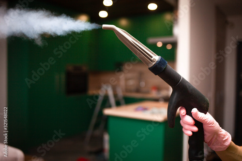 Fotografie, Tablou Closeup steam exiting nozzle of vapor cleaning machine at the hand