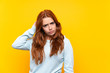 Teenager redhead girl over isolated yellow background having doubts