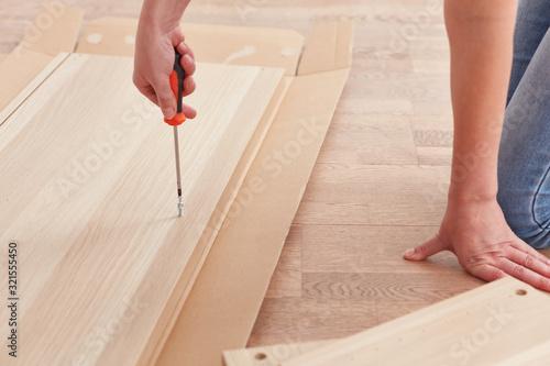 Woman assembling self-assembling furniture Tablou Canvas