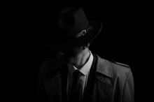 Black And White Low Key Portrait Of Young Gangster With Hat In The Darkness.