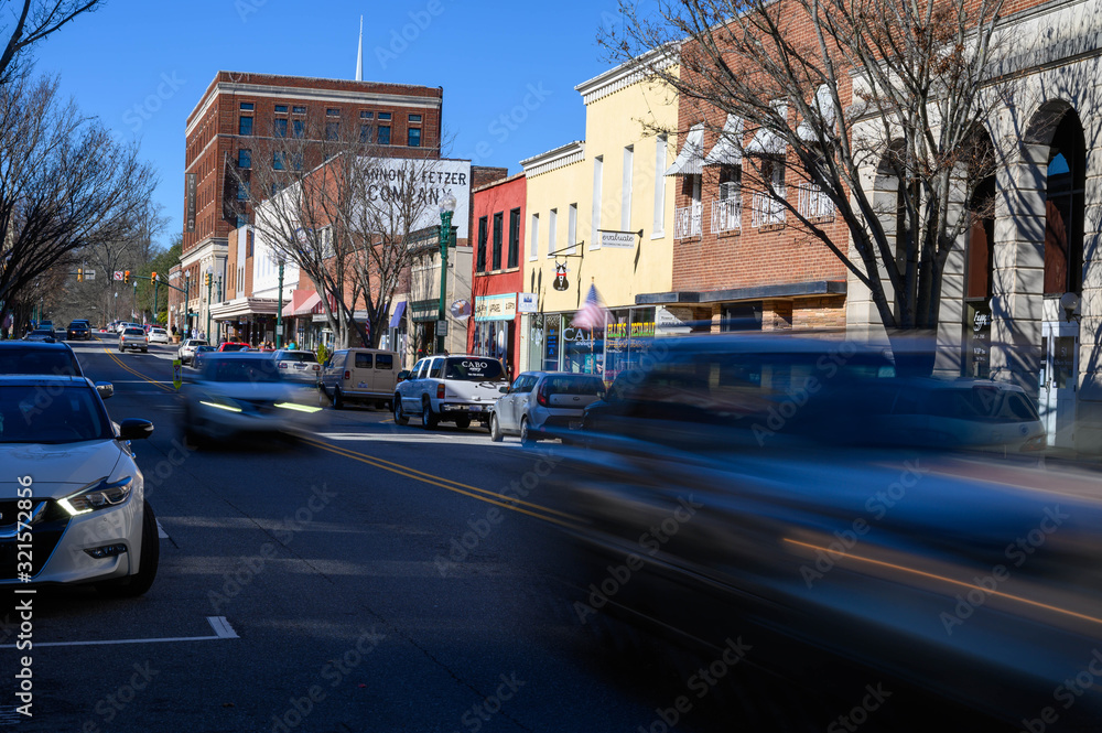 Fototapeta Looking down Union Street in downtown Concord NC. The blurred cars move down the main street.