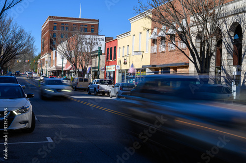 Obraz Looking down Union Street in downtown Concord NC. The blurred cars move down the main street. - fototapety do salonu