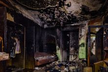 Burnt House Interior. Burned Furniture, Charred Walls And Ceiling In Black Soot