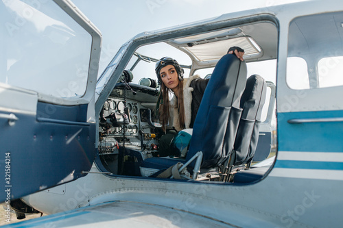 Fotografie, Obraz the girl in the place of the second pilot looks out of the cockpit with the side