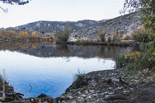 large lake reflecting autumn trees colors and the mountain