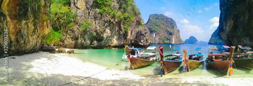 Island beach with limestone rocks and long tail boats